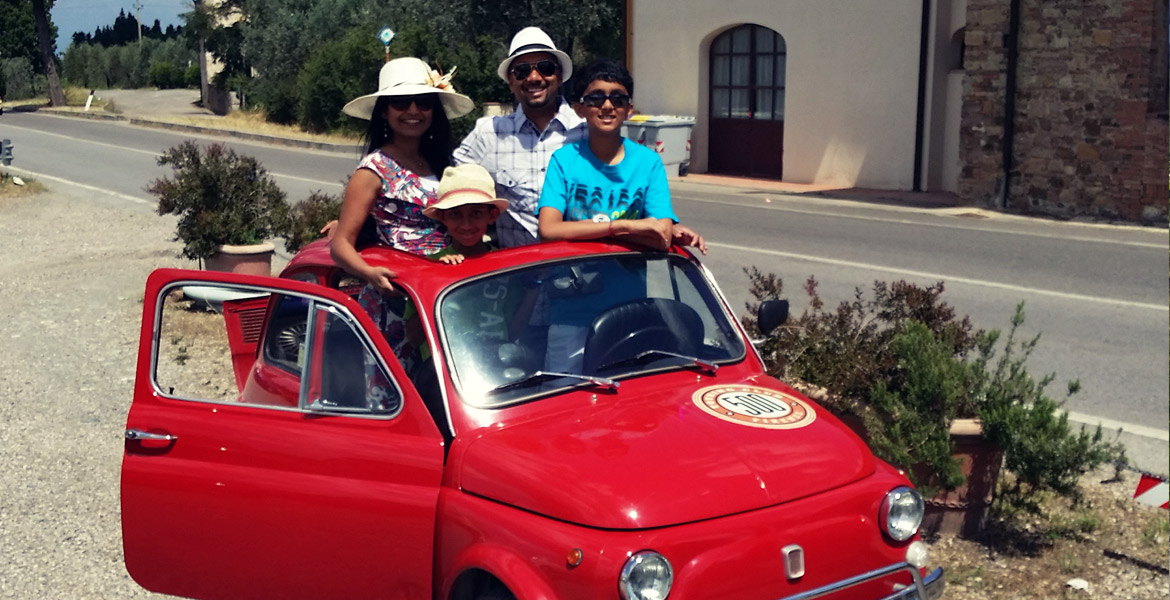 Family portrait on a vintage fiat 500 in Florence